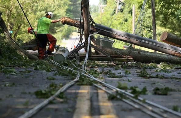 Workers cut up a fallen tree, so that power lines can be repaired, on June 30, 2012 in Huntington, Maryland. Over a million homes across the Washington area lost power after a severe thunderstorm hit the area. (Photo by Mark Wilson/Getty Images)