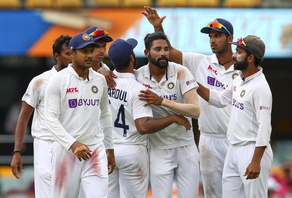 India's Mohammed Siraj, centre, is congratulated by teammates after taking his fifth wicket during play on day four of the fourth cricket test between India and Australia at the Gabba, Brisbane, Australia, Monday, Jan. 18, 2021. (AP Photo/Tertius Pickard)