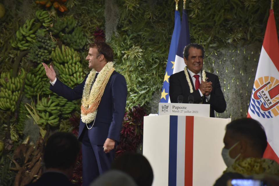 France's President Emmanuel Macron wearing a flower lei and seashell necklaces and French Polynesia Edouard Fritch acknowledge applauses after their speeches in Tahiti, French Polynesia in the Pacific Ocean, Tuesday, 27, 2021.President Emmanuel Macron reasserted France's presence in the Pacific on a visit to French Polynesia aimed in part at countering growing Chinese dominance in the region. (AP Photo/Esther Cuneo)