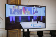 French President Emmanuel Macron, right on screen, attends a video-conference meeting with U.S. President Joe Biden and German Chancellor Angela Merkel, center, ahead of 2021 Munich Security Conference at the Elysee palace in Paris, Friday Feb. 19, 2021. (Benoit Tessier/Pool via AP)
