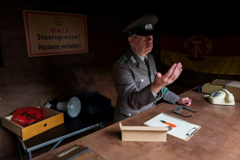 An actor dressed as an East German border police officer gestures to guests attending 'Socialist revival live cinema event', in Berlin