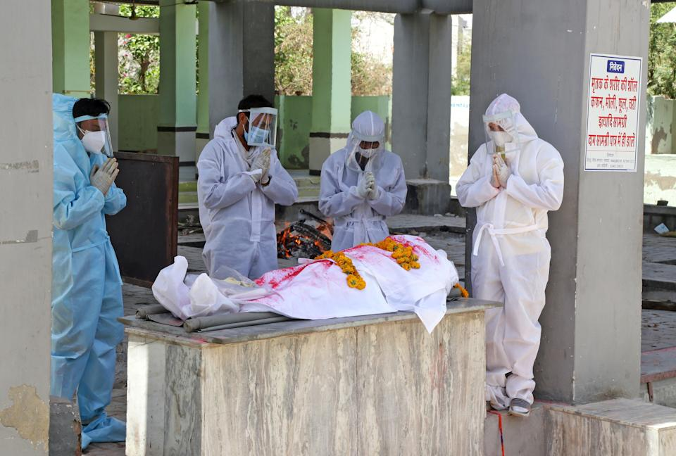 BEAWAR, RAJASTHAN, INDIA - 2021/04/23: (EDITORS NOTE: Image depicts death) Family members wearing protective suits, perform the last rites of a family memeber who died of COVID-19 at Hindu Moksha Dham crematorium in Beawar. (Photo by Sumit Saraswat/Pacific Press/LightRocket via Getty Images)