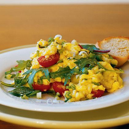 """<p>Mixed Asian greens, halved <a href=""""https://www.myrecipes.com/ingredients/vegetable-recipes/cherry-tomato-recipes"""" rel=""""nofollow noopener"""" target=""""_blank"""" data-ylk=""""slk:cherry tomatoes"""" class=""""link rapid-noclick-resp"""">cherry tomatoes</a>, grated Parmesan cheese, and chopped scallions give a little extra punch of flavor to classic scrambled eggs. Can't find mixed Asian greens? Feel free to substitute baby spinach instead. Serve with a slice of toasted French bread. </p>"""