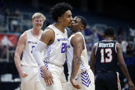 Abilene Christian guard Coryon Mason (20) and guard Damien Daniels, right, chest-bump after Mason was fouled on a dunk against Lamar during the first half of an NCAA college basketball game in the Southland Conference semifinals Friday, March 12, 2021, in Katy, Texas. (AP Photo/Michael Wyke)