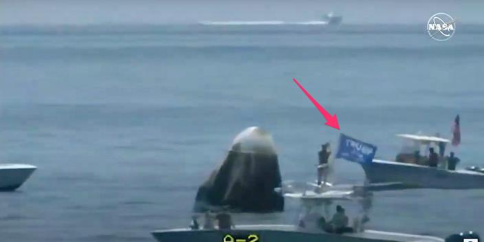 A boat with a person waving a Trump flag passes close to the Crew Dragon capsule after splashdown, August 2, 2020.