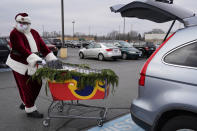 Santa Claus wears a mask as he pushes a sleigh full of curbside grocery orders to an Aldi customer at a parking lot in Palatine, Ill., Saturday, Dec. 19, 2020. For this weekend only, Santa Claus is delivering groceries to Aldi customers in Palatine and several other towns in the Chicago area. (AP Photo/Nam Y. Huh)