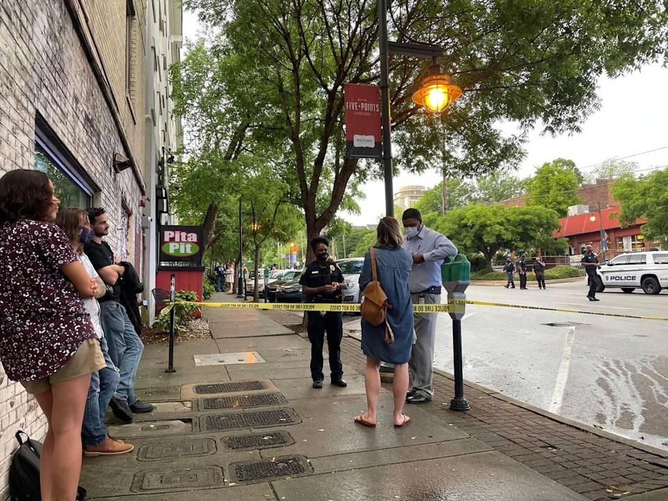 Rachel Ponder speaks with a Columbia police investigator about a shooting in Columbia's Five Points on Greene Street.
