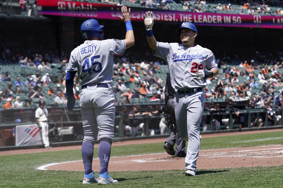 Los Angeles Dodgers' Matt Beaty (45) celebrates with Yoshi Tsutsugo (28) after both scored on a two-run double hit by Julio Urias against the San Francisco Giants during the second inning of a baseball game in San Francisco, Sunday, May 23, 2021. (AP Photo/Jeff Chiu)