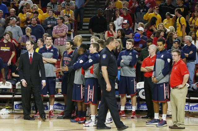 Arizona players and staff stand at their bench during the second overtime of an NCAA college basketball game against Arizona State, Friday, Feb. 14, 2014, in Tempe, Ariz. Arizona State defeated Arizona 69-66 in double overtime. (AP Photo/Ross D. Franklin)