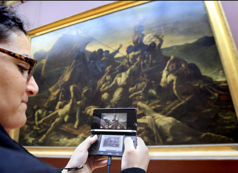 """A visitor studies a painting """"The Raft of the Medusa"""" by French artist Theodore Gericault 1791 - 1824 with the help of the new audio guide at the Louvre Museum in ParisThursday April 12, 2012. The famed Paris museum is going 3D visual with its electronic guides in a deal with Japan's Nintendo to provide game consoles to help visitors who navigate its labyrinthine halls by the millions each year. The guides, in seven languages, and accompanying headsets cost Euro5 ($6.50) on top of the museum's Euro10 standard admission price. (AP Photo/Jacques Brinon)"""