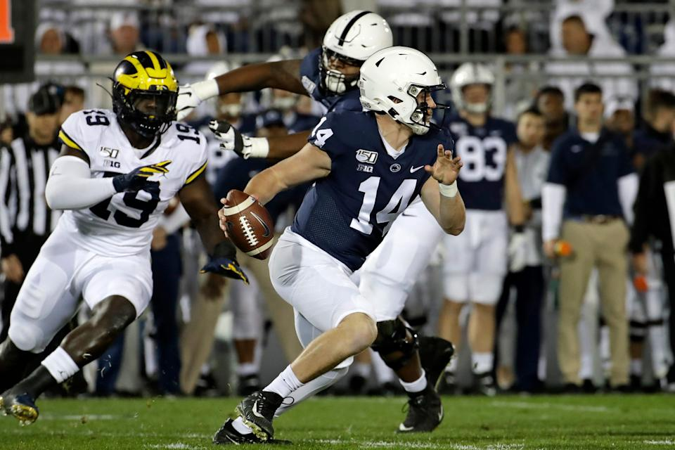 Penn State quarterback Sean Clifford runs for a first down as MIchigan's Kwity Paye chases during the first half against Michigan at Beaver Stadium, Saturday, Oct. 19, 2019.