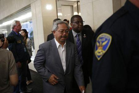 San Francisco Mayor Ed Lee leaves after a news conference at San Francisco International Airport