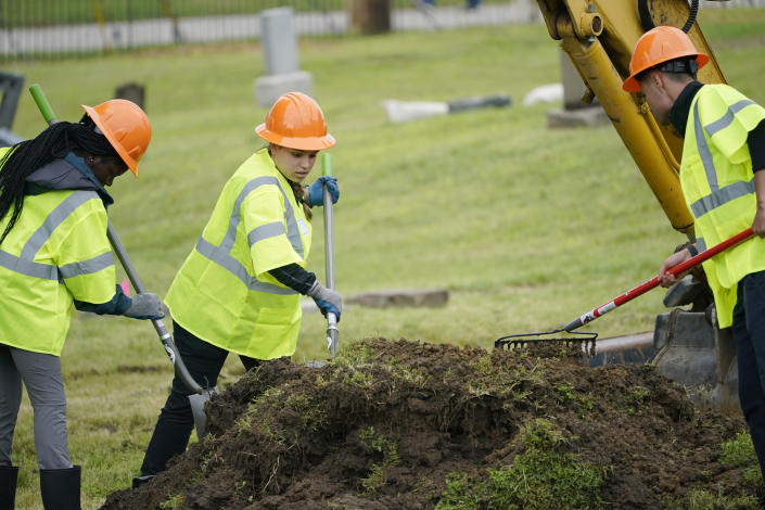 Workers rake through dirt as excavation begins at Oaklawn Cemetery in a search for victims of the Tulsa Race Massacre believed to be buried in a mass grave, Tuesday, June 1, 2021, in Tulsa, Okla. (AP Photo/Sue Ogrocki)