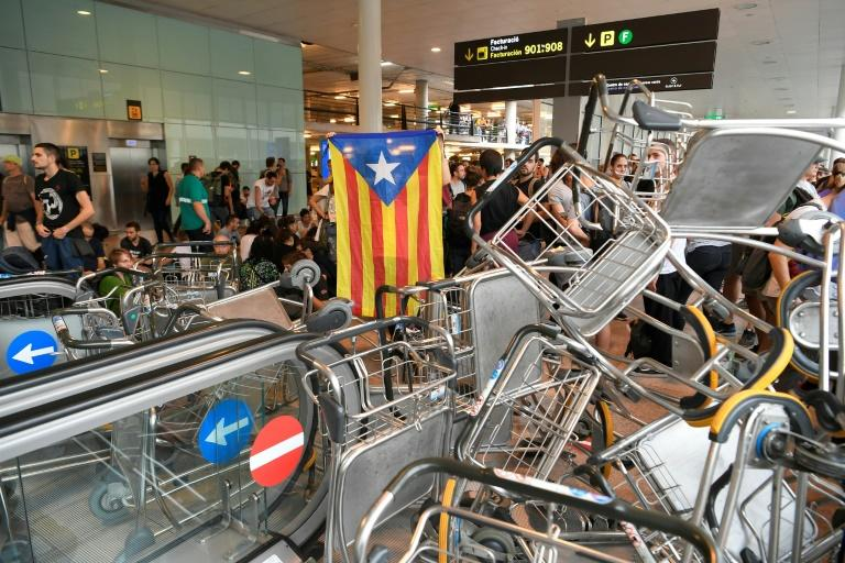 Demonstrators used luggage trolleys to block escalators at the airpor (AFP Photo/LLUIS GENE)