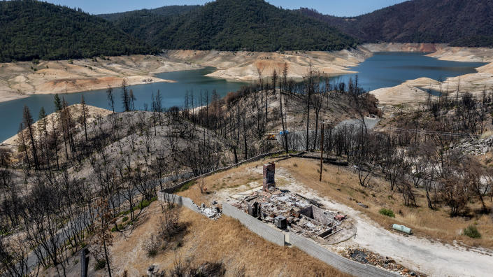 A home destroyed in the 2020 North Complex Fire sits above Lake Oroville on Sunday, May 23, 2021, in Oroville, Calif. At the time of this photo, the reservoir was at 39 percent of capacity and 46 percent of its historical average. California officials say the drought gripping the U.S. West is so severe it could cause one of the state's most important reservoirs to reach historic lows by late August, closing most boat ramps and shutting down a hydroelectric power plant during the peak demand of the hottest part of the summer. (AP Photo/Noah Berger)