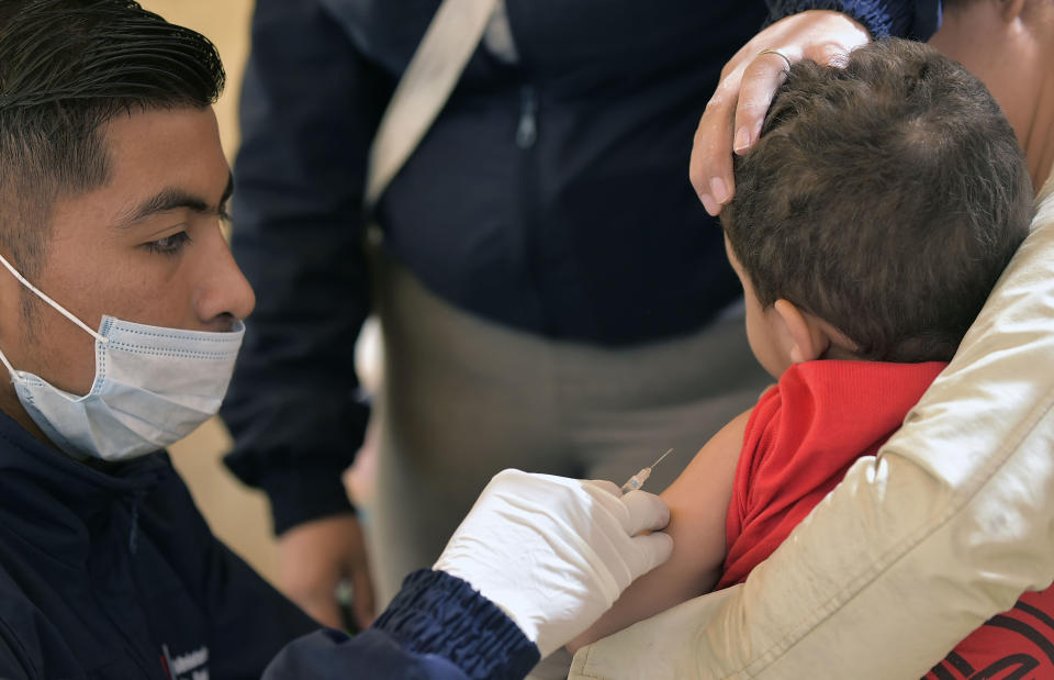 A Venezuelan migrant child receives a vaccine after crossing from Colombia, at an Ecuadoran Health Ministry attention centre at the Rumichaca international bridge in Tulcan, Ecuador on August 11, 2018. - The