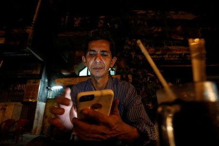 Vietnamese deportee and Amerasian Pham Chi Cuong, 47, who was deported from the U.S., uses his mobile phone while having a coffee in central Ho Chi Minh City, Vietnam April 20, 2018. REUTERS/Kham