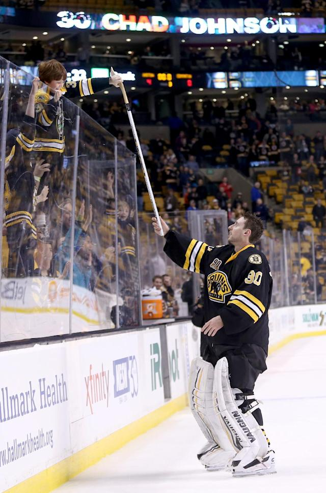 Boston Bruins goalie Chad Johnson (30) hands his stick to a fan after posting a shutout in a 4-0 win over the Edmonton Oilers in an NHL hockey game, Saturday, Feb. 1, 2014 in Boston. (AP Photo/Mary Schwalm)