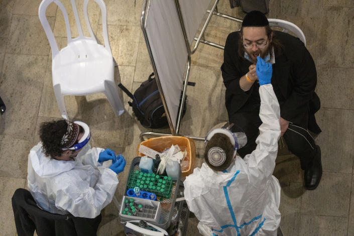 Medical personnel test a passenger for coronavirus on his arrival in Israel, at Ben Gurion Airport near Tel Aviv, Israel, Sunday, Jan. 24, 2021, during a nationwide lockdown to curb the spread of the COVID-19 virus. (AP Photo/Ariel Schalit)