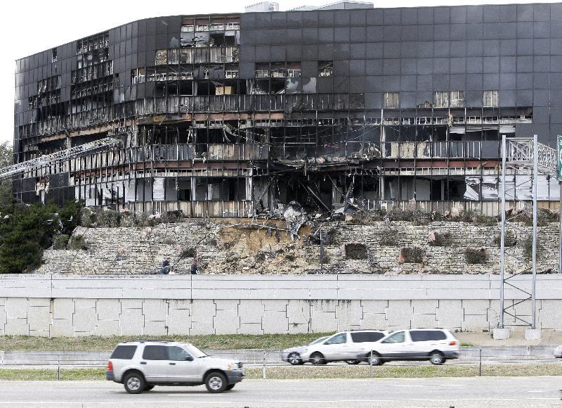 FILE - This Feb. 18, 2010 file photo shows vehicle traffic on U.S. Highway 183 in front of a damaged building in Austin, Texas where authorities said a man flew his small plane into the building that housed several employees of the IRS. For a time, the Internal Revenue Service inspired awe and admiration in Americans, not just trepidation and lame jokes about death and taxes. But there's little love for the IRS anymore and there hasn't been for ages. (AP Photo/Tony Gutierrez, File)
