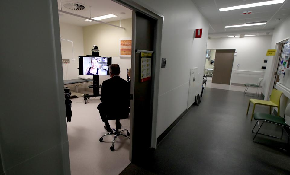 A doctor utilising a new video conferencing clinic at the Royal Adelaide Hospital to speak with a cystic fibrosis patient who is up on a TV screen.