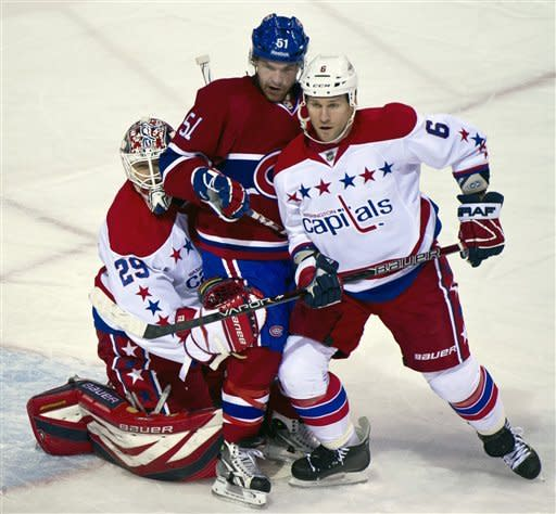 Montreal Canadiens' David Desharnais gets caught in between Washington Capitals goalie Tomas Vokoun, left, and defenseman Dennis Wideman during first period NHL hockey action, Saturday, Feb. 4, 2012 in Montreal. (AP Photo/The Canadian Press, Paul Chiasson)