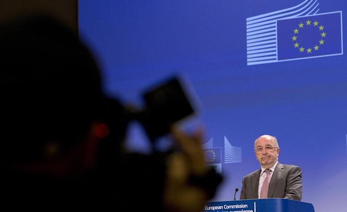 European Commissioner for Competition Joaquin Almunia, right, grimaces during a media conference at EU headquarters in Brussels on Monday, Jan. 13, 2014. The European Union's antitrust watchdog says it has opened an investigation on licensing agreements between several major U.S. film studios and European pay TV broadcasters. Its probe covers Twentieth Century Fox, Warner Bros., Sony Pictures, NBCUniversal and Paramount Pictures. (AP Photo/Virginia Mayo)