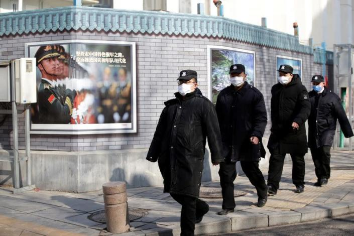 Security personnel wearing masks walk along the Financial Street in central Beijing
