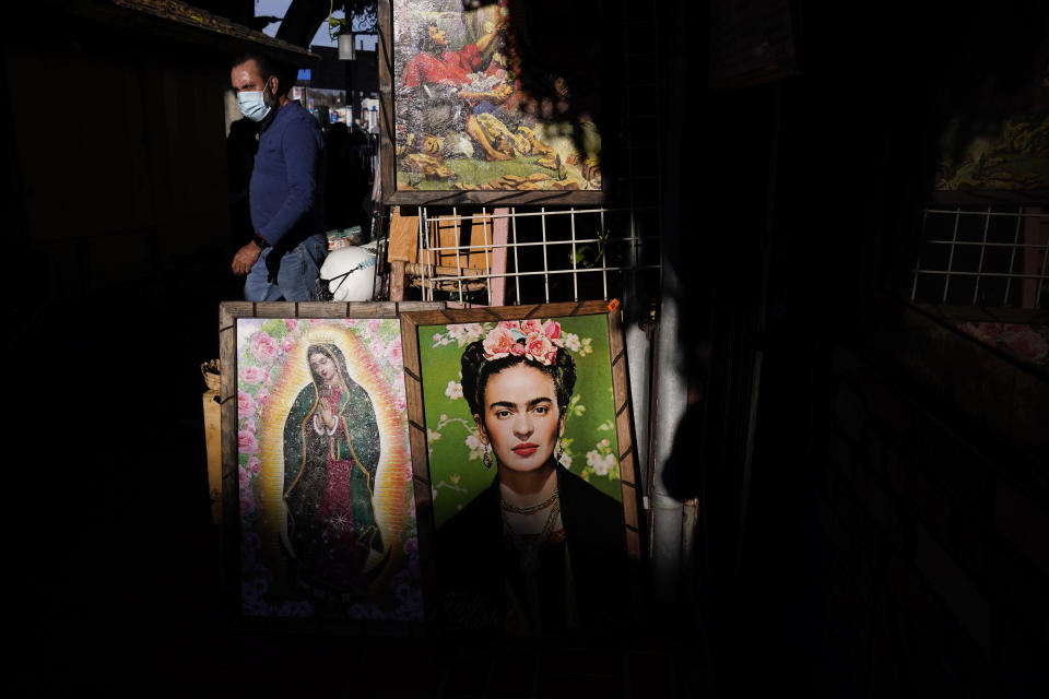 Framed paintings depicting Our Lady of Guadalupe and Mexican artist Frida Kahlo are placed outside a gift shop on Olvera Street in downtown Los Angeles, Wednesday, Dec. 16, 2020. The tree-covered brick alley typically teeming with tourists is empty. Many of the shops that sell everything from traditional Mexican folk dresses to paintings of artist Frida Kahlo to sombreros are padlocked and the ones open have few, if any, customers. (AP Photo/Jae C. Hong)