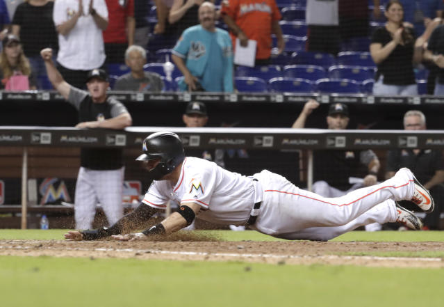 Miami Marlins' Miguel Rojas scores the game-winning run on a sacrifice fly by Brian Anderson during the ninth inning of a baseball game against the San Francisco Giants, Wednesday, June 13, 2018, in Miami. The Marlins won 5-4. (AP Photo/Lynne Sladky)
