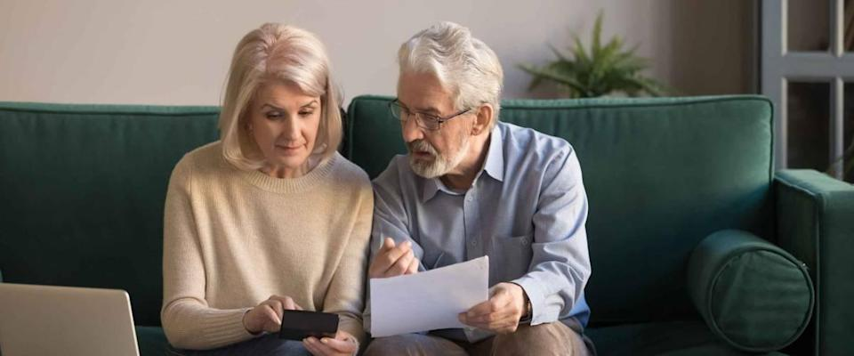 Serious mature couple calculating bills to pay, checking domestic finances.