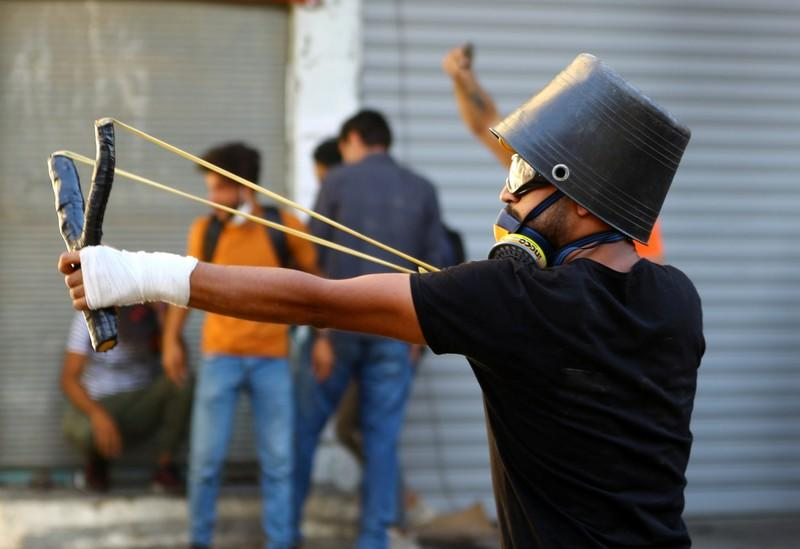 A demonstrator uses a slingshot during the ongoing anti-government protests in Baghdad