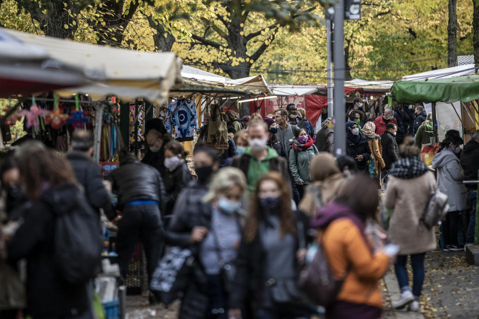 "BERLIN, GERMANY - OCTOBER 27: People wear protective masks as they shop at an outside market in the Neukoelln district during the second wave of the coronavirus pandemic on October 27, 2020 in Berlin, Germany. According to media reports the German government is considering a ""lockdown light"" that would include temporarily closing restaurants and bars but keeping schools and child day care centers open in an attempt to rein in the recent sharp rise in infections. Germany is currently averaging over 10,000 new confirmed cases of coronavirus infections per day. (Photo by Maja Hitij/Getty Images)"