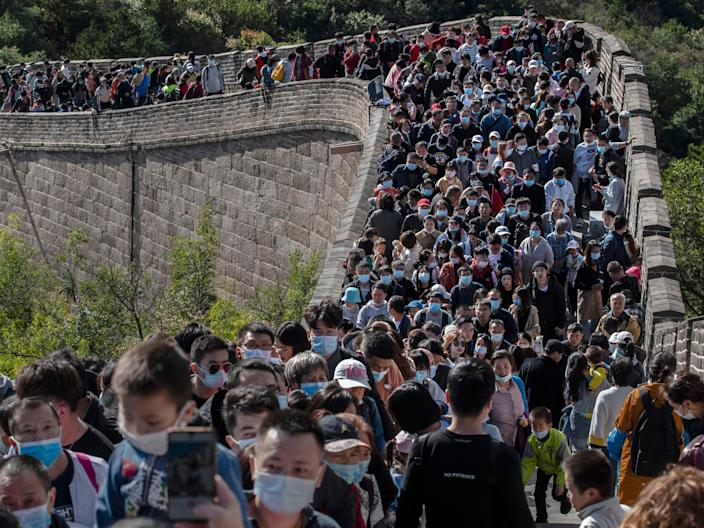 BEIJING, CHINA - OCTOBER 04: Chinese tourists crowd in a bottleneck as they move slowly on a section of the Great Wall at Badaling after tickets sold out during the 'Golden Week' holiday on October 4, 2020 in Beijing, China. Officials are expecting the Golden Week holiday to boost China's consumer economy as people were encouraged to use the 8-day break to travel and spend. Tourist sites including the Great Wall were packed, with tickets selling out most days given pandemic restrictions and capacity capped at 75%. (Photo by Kevin Frayer/Getty Images)