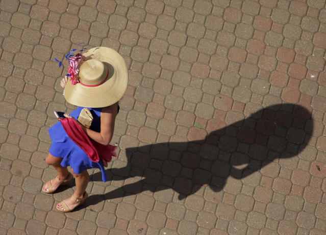 A woman arrives before the 140th running of the Kentucky Derby horse race at Churchill Downs Saturday, May 3, 2014, in Louisville, Ky. (AP Photo/Charlie Riedel)