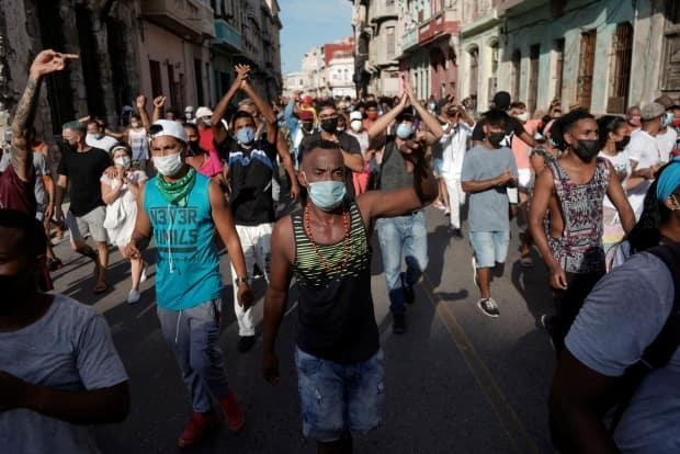 People shout anti-government slogans during a protest on Sunday in Havana, Cuba. (Alexandre Meneghini/Reuters - image credit)