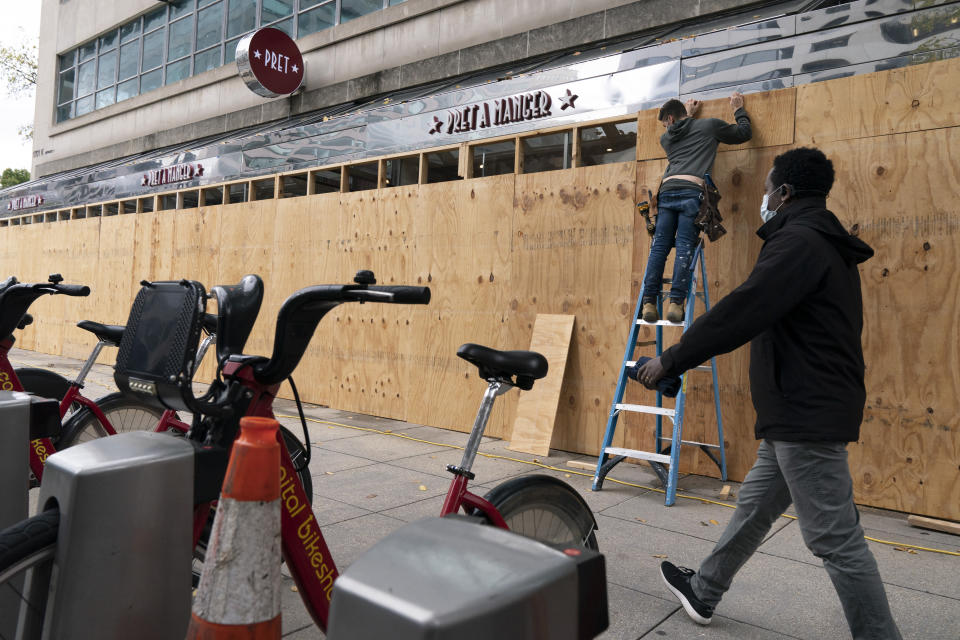 A pedestrian passes work being done to board up a Pret A Manger restaurant along K Street, Friday, Oct. 30, 2020, ahead of the presidential election, in downtown Washington not far from the White House. (AP Photo/Jacquelyn Martin)