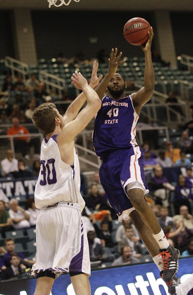 Northwestern State center Marvin Frazier Jr. (40) drives to the basket over Stephen F. Austin's Tanner Clayton (30) during the first half of an NCAA college basketball game in the semifinal round of the Southland Conference tournament Friday, March 14, 2014, in Katy. (AP Photo/Bob Levey)