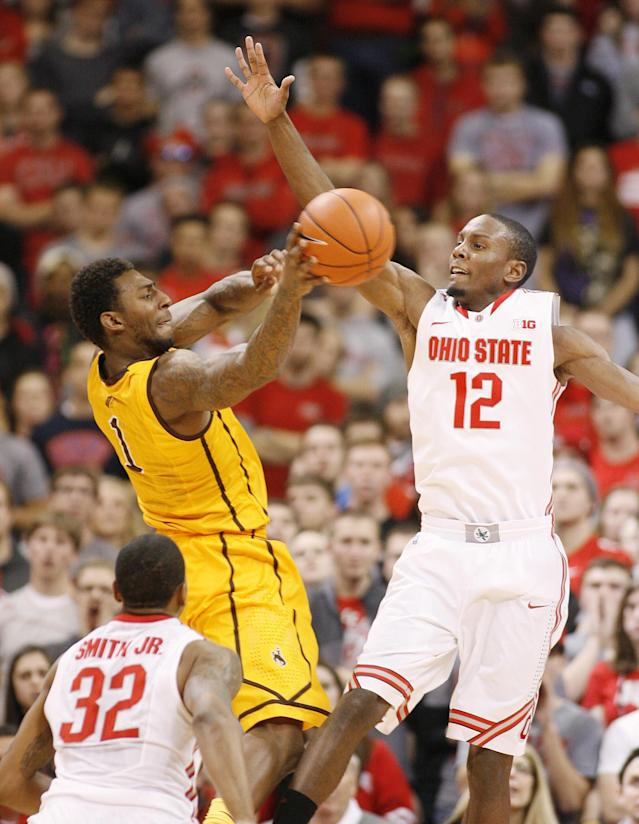 Wyoming's Charles Hankerson (1) passes around Ohio State's Sam Thompson (12) during the second half of an NCAA college basketball game, Monday, Nov. 25, 2013, in Columbus, Ohio. (AP Photo/Mike Munden)