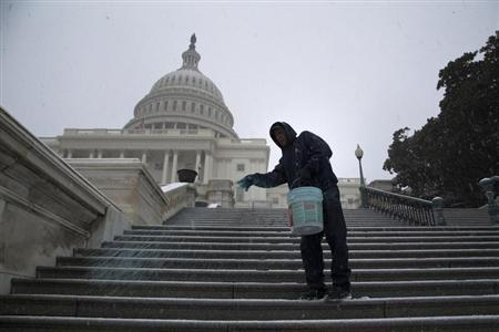 A worker spreads an anti-ice mix on the steps of the U.S. Capitol as light snow flurries fall in Washington
