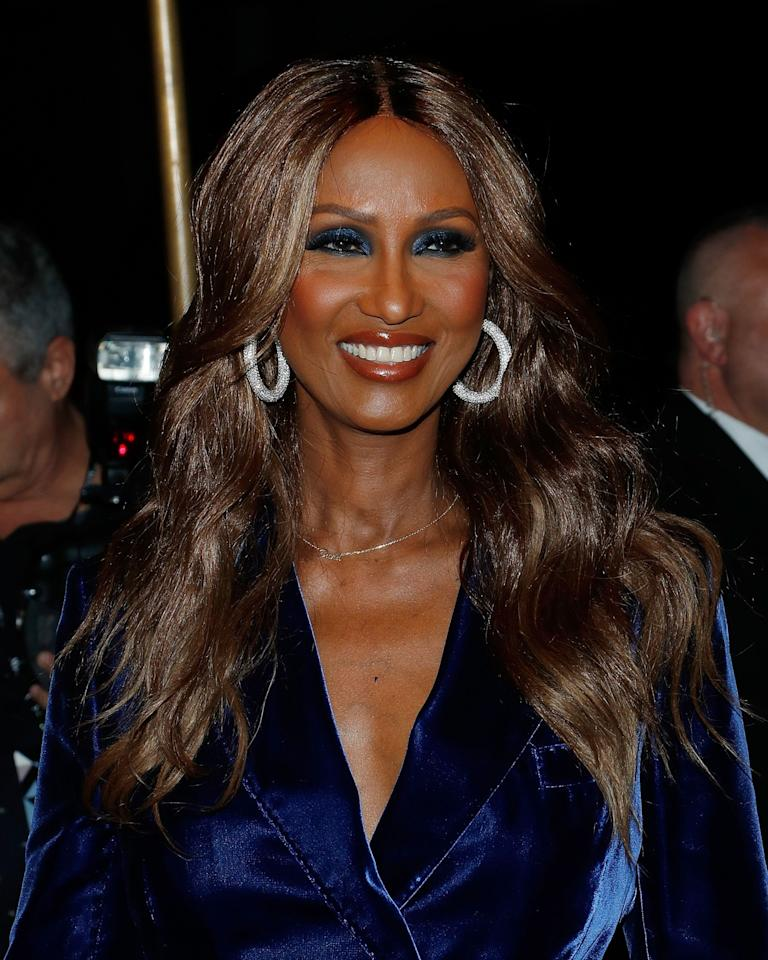 <p>Iman stepped out at the Tom Ford fashion show wearing sun-kissed bronzer, midnight blue eyeshadow that matched her velvet suit, and burnished orange lip gloss. (Photo: Getty Images) </p>