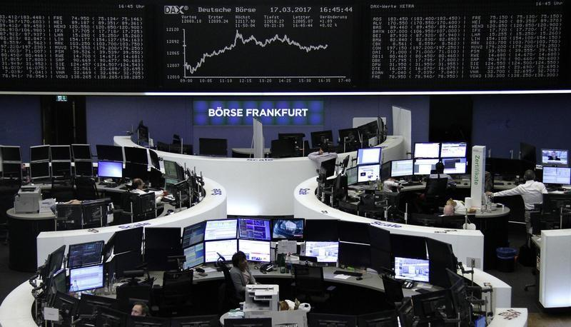 Traders work at their desks in front of the German share price index, DAX board, at the stock exchange in Frankfurt, Germany, March 17, 2017. REUTERS/Staff/Remote