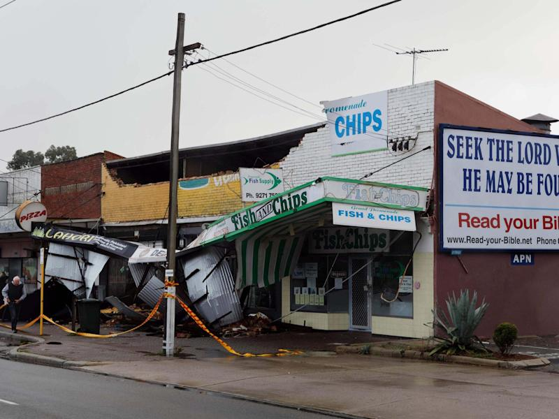 A man (L) walks past shops roped off after they sustained damage in the Perth suburb of Bedford after the area was lashed by gale force winds and a tidal surge from the remnants of Tropical Cyclone Mangga: AFP via Getty Images