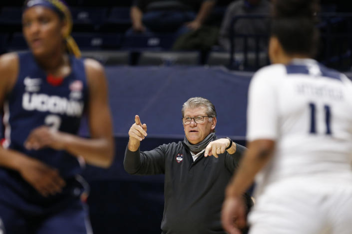 Connecticut head coach Geno Auriemma, center, directs his team against Xavier during the second half of an NCAA college basketball game Saturday, Feb. 20, 2021, in Cincinnati. UConn won 83-32. (AP Photo/Gary Landers)