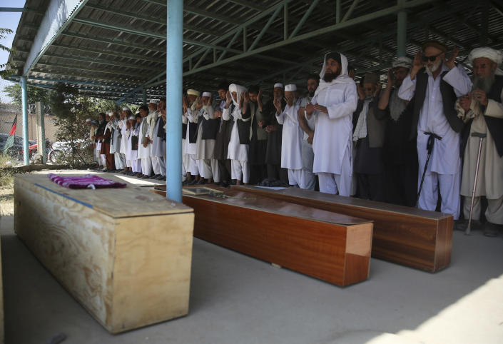 Afghans pray near the coffins of victims of the Dubai City wedding hall bombing during a mass funeral in Kabul, Afghanistan, Sunday, Aug.18, 2019. The deadly bombing at the wedding in Afghanistan's capital late Saturday that killed dozens of people was a stark reminder that the war-weary country faces daily threats not only from the long-established Taliban but also from a brutal local affiliate of the Islamic State group, which claimed responsibility for the attack. (AP Photo/Rafiq Maqbool)