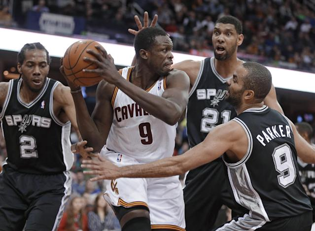 Cleveland Cavaliers' Luol Deng (9) is surrounded by San Antonio Spurs' Kawhi Leonard (2), Tim Duncan (21) and Tony Parker (9) during the third quarter of an NBA basketball game Tuesday, March 4, 2014, in Cleveland. The Spurs won 122-101. (AP Photo/Mark Duncan)
