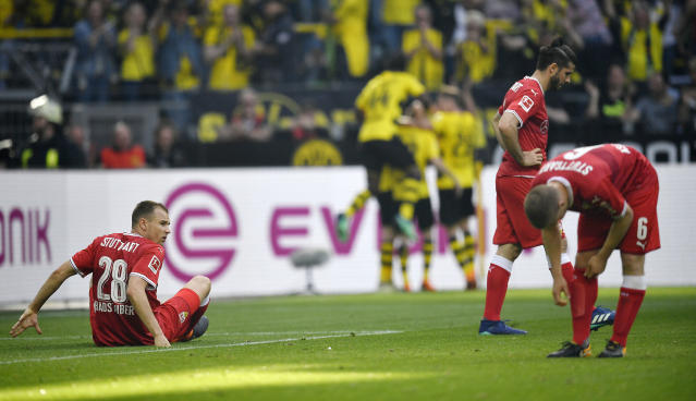Stuttgart's Holger Badstuber is on the ground disappointed after they received the third goal during the German Bundesliga soccer match between Borussia Dortmund and VfB Stuttgart in Dortmund, Germany, Sunday, April 8, 2018. (AP Photo/Martin Meissner)