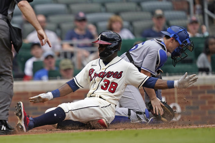 Atlanta Braves' Guillermo Heredia (38) scores ahead of the throw to Los Angeles Dodgers catcher Will Smith, right, on a sacrifice fly by Ender Inciarte in the eighth inning of a baseball game Sunday, June 6, 2021, in Atlanta. (AP Photo/Brynn Anderson)