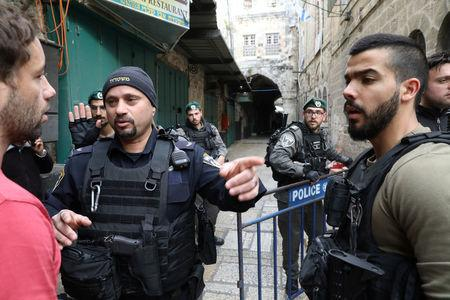 Israeli security forces block a man from entering an alley following a stabbing attack inside the old city of Jerusalem