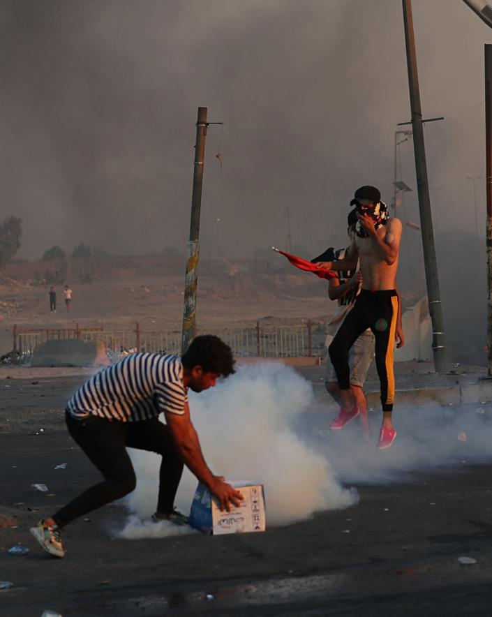 Iraqi security forces fire tear gas to disperse anti-government protesters during a demonstration in Baghdad, Iraq, Saturday, Oct. 5, 2019. Iraqi protesters pressed on with angry anti-government rallies across several provinces, in some cases torching party offices, for the fifth day, ignoring appeals for calm from political and religious leaders. Security agencies kept up their heavy crackdown, firing live ammunition and killing more than 14 protesters Saturday. (AP Photo/Hadi Mizban)